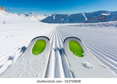 Pair of new skis standing on the fresh snow on newly groomed ski slope at ski resort on a sunny winter day.