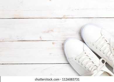 Pair of new white sneakers on white wooden background.