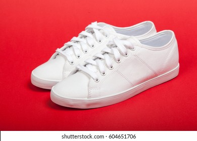 Pair of new white sneakers on red background