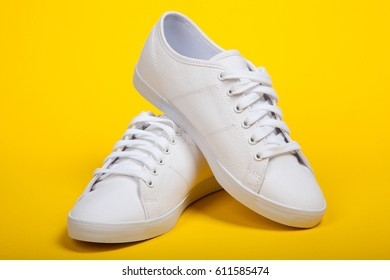 Pair of new white sneakers on yellow background