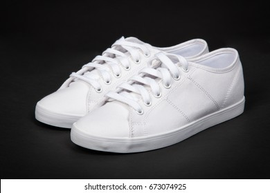 Pair of new white sneakers on black background