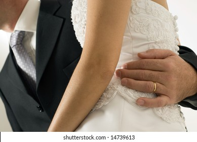 A pair of newly weds, sit on a chair, the woman in the mans lap, with the mans arm around her back. - horizontally framed