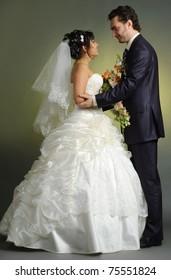 Pair newlyweds bridegroom and bride pose in studio