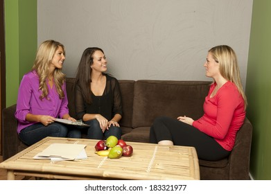 A pair of nutritionist consult a pregnant female on a couch.