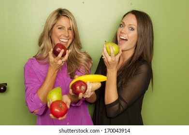 A pair of nutritionists posing on a green background holding a variety of fruits.