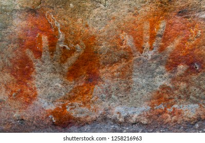 A pair of ochre hands, Red, Orange, Yellow hand prints on a rock, Aboriginal art in Queensland, Australia.