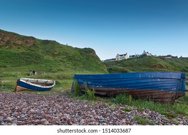 A pair of old abandoned open Wooden fishing Boats lie on the beach below the Cliff top Village of Auchmithie, near Arbroath, in Angus, Scotland.