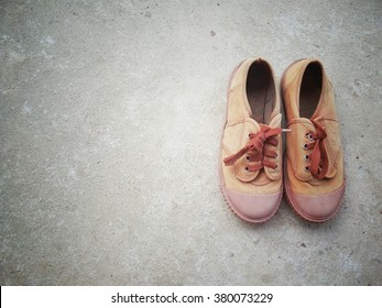 pair of old brown shoes for school on cement background, vintage tone