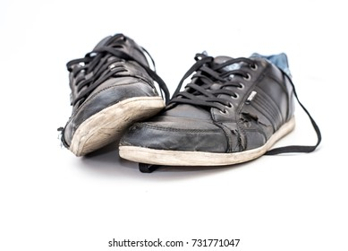 Pair of old dirty black sneakers isolated on white