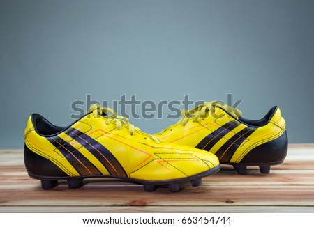 a124a9bfc A pair of old football boots old yellow football shoes placed on a wooden  board,