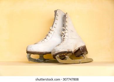 Pair of old ice Skates on yellow shelf