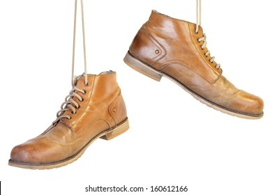 A pair of old leather boots with laces hanging