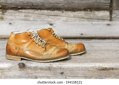 A pair of old leather boots on background wooden wall of a house