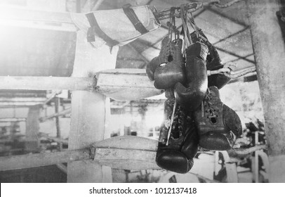 A pair of old Muay Thai boxing gloves hangs on the boxing ring in a slum camp.Vintage effect added for create atmosphere