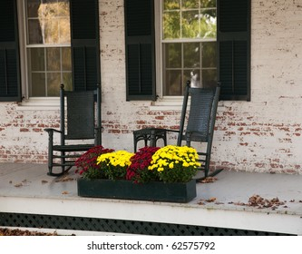 Pair of old rocking chairs on porch of old building in fall