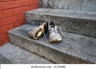A pair of old running shoes on cement steps with a red brick wall as a background.