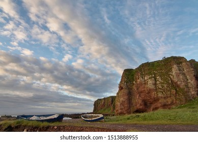 A Pair of old Scottish Wooden Fishing Boats lie beneath the Cliffs on Auchmithie beach off the North East Coast of Scotland, near Arbroath.