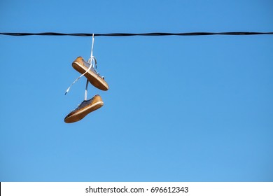 Pair of old shoes hang on power line against blue sky, space for text.