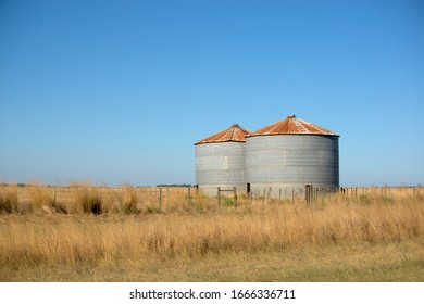 pair of old silos for cereal storage in a field