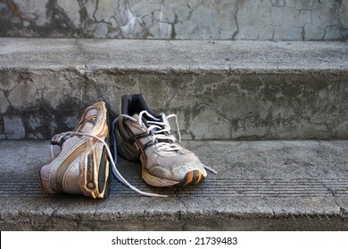A pair of old used  running shoes on cement steps.