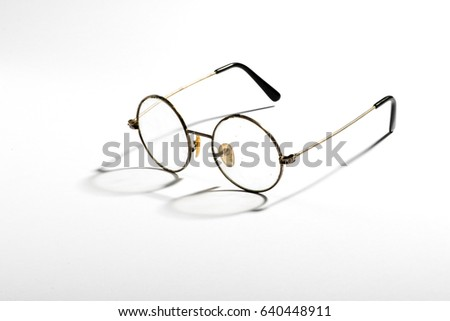 82b244fd59c7 Pair of old vintage spectacles with wire frames and round lenses displayed  casting a shadow on