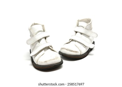 a pair of old white kid's orthopedic footwear isolated on white