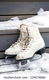 Pair of old white skates on snowy wooden stairs