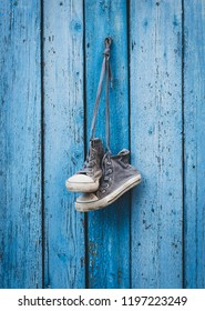 pair of old worn black textile sneakers hangs on a nail, shoes are very worn, blue wooden background