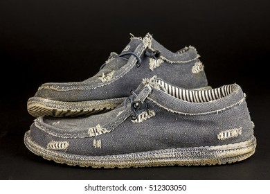 Pair of old and worn out  shoes on black background/Worn out shoes