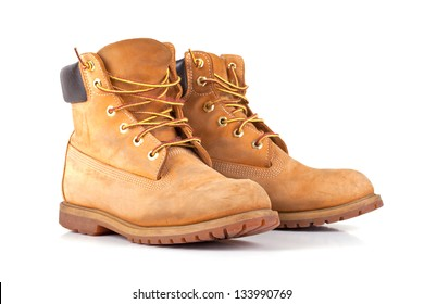 Pair of old yellow working boots Isolated on white background