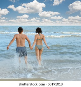 Pair on seacoast. The enamoured guy and the girl walking on coast