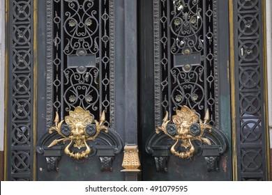 A pair of ornate golden lion head door knockers