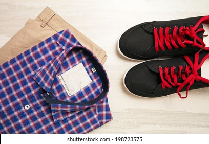 a pair of pants, a checked shirt and casual canvas shoes on old background
