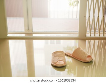 A pair of pastel pink house slippers at home front gate on lazy Sunday morning , single concept