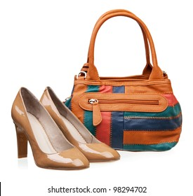 Pair of patent leather women shoes and bag over white