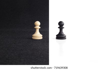 Pair of peon chess peaces confronted as opposites in black and white background.