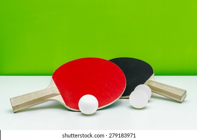 Pair of ping-pong rackets and white balls, isolated on light gre