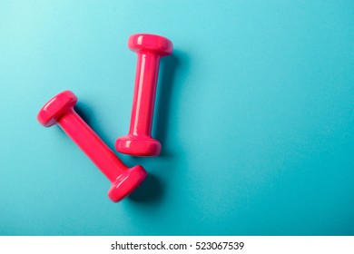 Pair of pink 1 kg dumbbells on blue background and water bottle