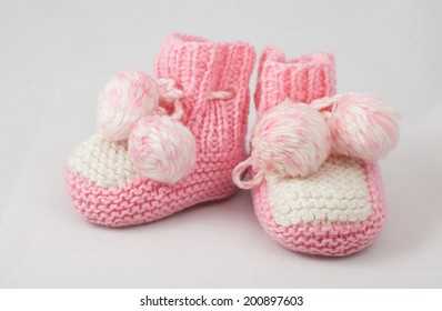 a pair of pink baby's bootees