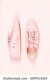 Pair of pink canvas sneakers on pink background, top view, flat lay. Trendy fashion pastel Woman shoes. Copyspace