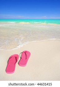A pair of pink flip-flop sandals on a stunning white sand tropical beach. Travel & vacation concepts.