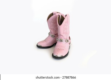 Pair of pink leather cowgirl boots on white background.
