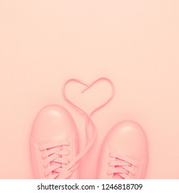 Pair of pink shoes with heart made of shoelaces on pink background. Trendy pastel color, monochrome image. Valentine's card concept.