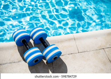 Pair of plastic dumbbells for aqua fitness lying near swimming pool on summer day outdoors, top view, nobody