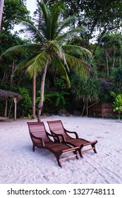 A pair of polished wooden lounge chairs on a white sand beach below coconut trees.