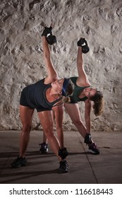 Pair of pretty women lifting kettlebell weights over their shoulders