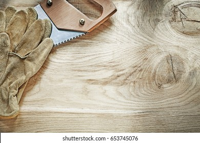 Pair of protective gloves sharp handsaw on wooden board construction concept.