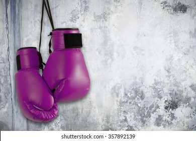 Pair of purple boxing gloves hanging on wall