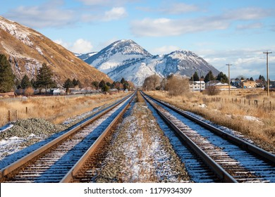 A pair of railroad tracks receding into the distant snow covered mountains.