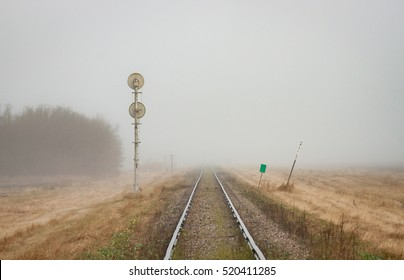 A pair of rails recede into the distant prairie fog